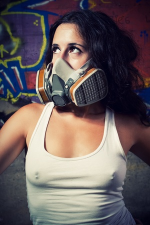 Pretty young girl in respirator posing over wall with graffiti