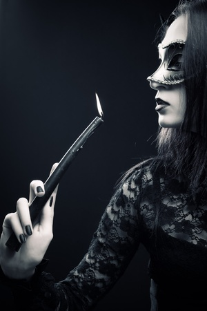 Pretty gothic girl in mask holding candle over dark background