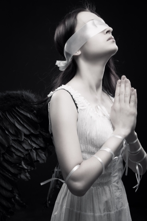 Pretty girl with artificial wings praying over dark background