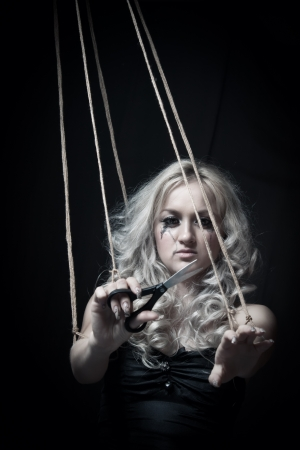 Glamourous girl with scissors cutting off ropes over dark background
