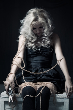 Pretty gothic girl with ropes sitting in the dark room