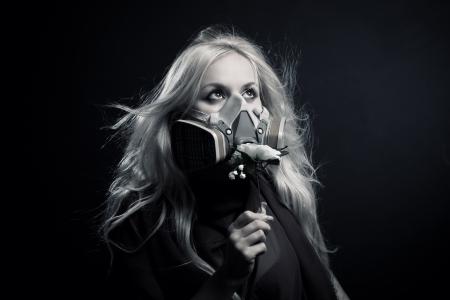 Pretty girl in respirator holding flower over dark background