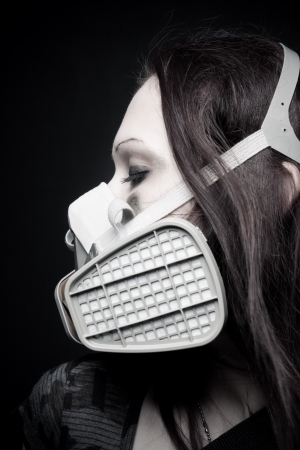 Pretty girl in respirator posing over dark background