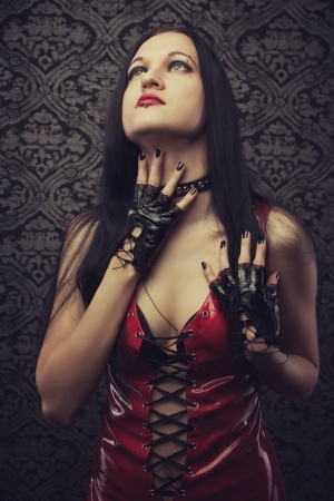 Gothic girl in red latex dress over vintage background