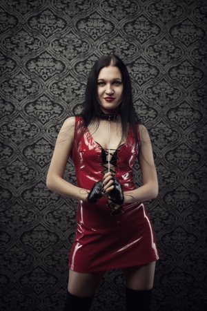 Attractive girl in red latex dress over vintage background