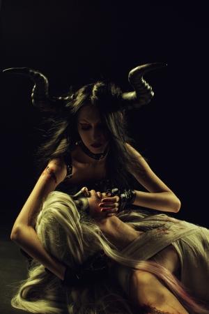 Seductive horned girl  holding head of fallen angel  Black