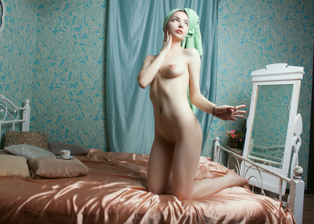 Photo pour Seductive nude girl posing on a bed with towel on her head - image libre de droit