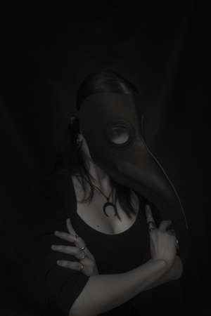 Photo pour Girl in plague doctor mask posing over dark background - image libre de droit