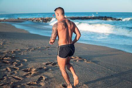 Foto de Tattooed bodybuilder sexy male coach at the beach. - Imagen libre de derechos