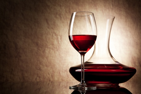 Photo pour decanter with red wine and glass on a old stone background - image libre de droit