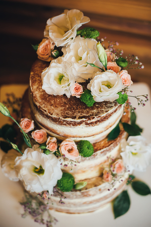 Photo pour Wedding cake with roses whipped cream on a wooden background - image libre de droit