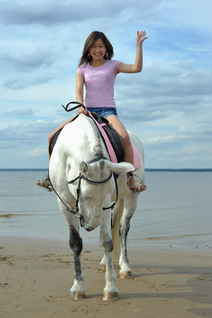 Photo for Young asian woman riding white horse on the beach - Royalty Free Image