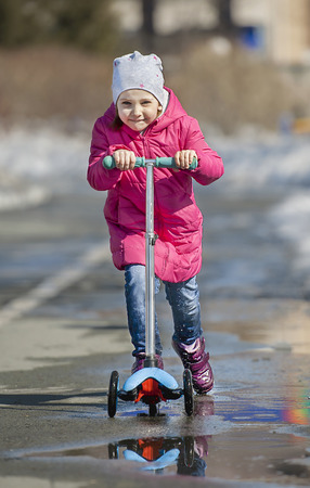 Foto de Child riding scooter. Kid on colorful kick board. Active outdoor fun for kids. Sports for preschool children. Little happy girl in spring park. The concept of a healthy lifestyle - Imagen libre de derechos