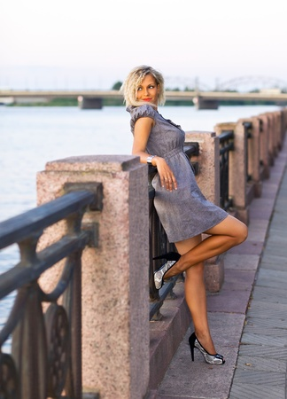 blond sexy woman in grey dress on a quay.