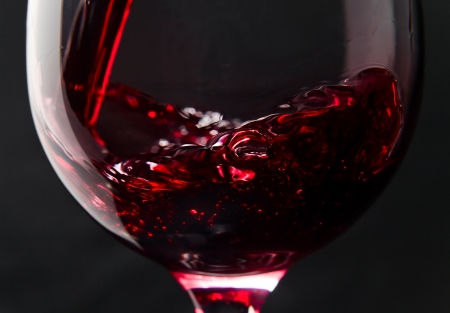 Photo pour Red wine in wineglass on a black background - image libre de droit