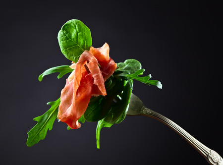 jamon with spinach and  arugula on dark background