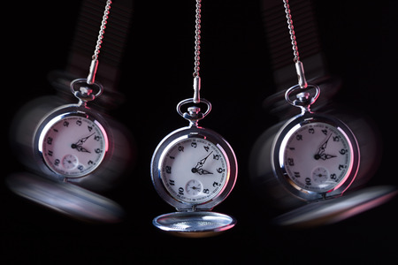 Foto de Pocket watch swinging on a chain to hypnotise , black background - Imagen libre de derechos