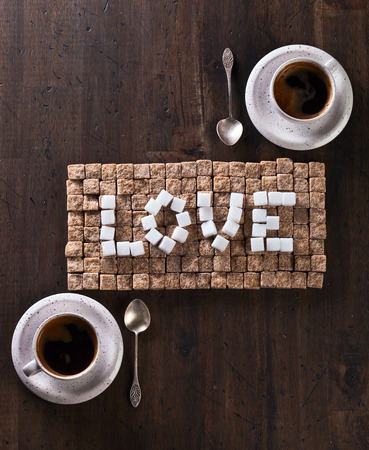word love made of brown and white sugars and cups of coffee