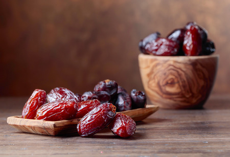Foto de Juicy dates in a bowl on a old wooden table . - Imagen libre de derechos
