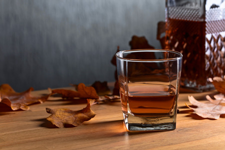 Foto per Whiskey and dried up oak leaves on a old wooden table. Copy space . - Immagine Royalty Free