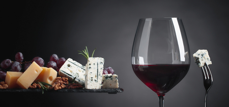 Photo for Glass of red wine with various cheeses, grapes, walnuts and rosemary on a dark background. Copy space . - Royalty Free Image