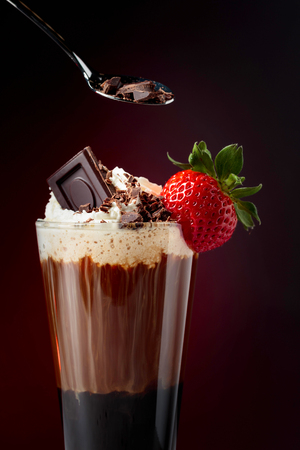Foto de Chocolate drink with whipped cream, strawberry and pieces of black chocolate on a dark background. Copy space. - Imagen libre de derechos