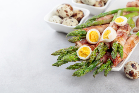 Photo for Asparagus with bacon. Green asparagus wrapped in bacon with boiled quail eggs. Copy space. - Royalty Free Image