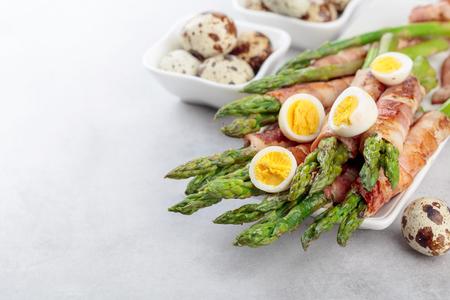 Foto de Asparagus with bacon. Green asparagus wrapped in bacon with boiled quail eggs. Copy space. - Imagen libre de derechos
