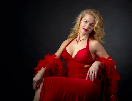 Photo pour Attractive smiling mature woman  in red evening dress with fluffy feather boa. Happy forty years blonde on a black background. Copy space. - image libre de droit
