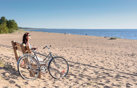 Foto de Middle-aged woman came on a Bicycle to the beach and resting sitting on a bench. Sunny summer evening on a sandy beach. - Imagen libre de derechos
