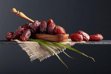 Foto de Closeup sweet dried dates in wooden dish. Copy space. - Imagen libre de derechos