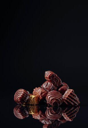 Photo pour Various chocolate candies on a black reflective background. Copy space. - image libre de droit