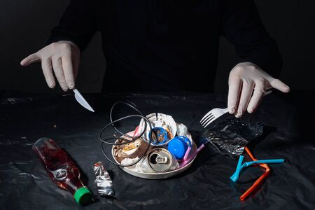 Photo pour Lunch. Man in rubber gloves at the table. On the table, plastic waste and various garbage. Concept on the theme of environment and pollution. - image libre de droit