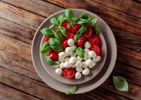 Photo pour Caprese salad with tomato, mini mozzarella and basil on a old wooden table. Italian food and healthy vegetarian diet. - image libre de droit