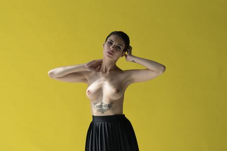 young beautiful girl posing nude in studio, standing in black skirt near yellow wall