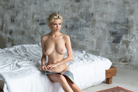 Foto de young beautiful girl posing nude in studio sitting on the bed - Imagen libre de derechos