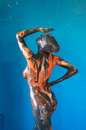 Photo for young beautiful girl posing black and orange paint - Royalty Free Image