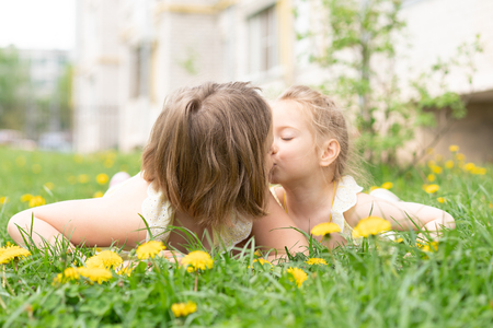 Photo for two girls are lying on yellow grass - Royalty Free Image