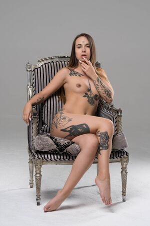 Photo for young beautiful girl posing nude in studio sitting on an armchair - Royalty Free Image