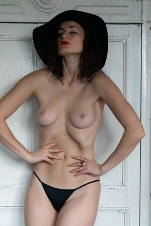 Photo pour Young beautiful girl pose nude in studio, stands in a black hat and black shorts. - image libre de droit