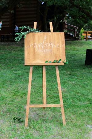 Foto de Wooden easel with a board. On the board written white paint - Welcome - Imagen libre de derechos