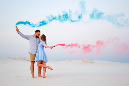 Foto de young couple kissing and holding colored smoke in hands, romantic couple with blue color and red color smoke bomb on beach - Imagen libre de derechos