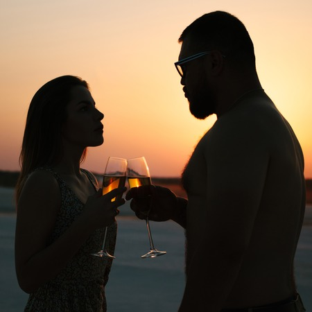 Foto de silhouette of a couple with glasses on sunset background, man and woman clanging wine glasses with champagne at sunset dramatic sky background - Imagen libre de derechos
