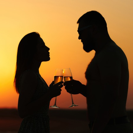Foto de silhouettes of man and woman, happy couple in love on the beach at the sunset, looking each other, smiling and holding in their hands glasses of champagne - Imagen libre de derechos