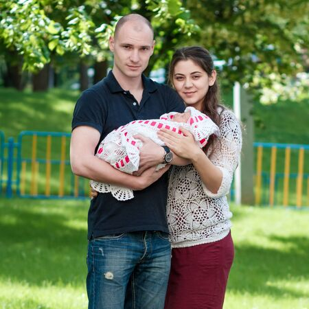Photo pour Happy couple holding their newborn daughter in her arms. Outdoors - image libre de droit