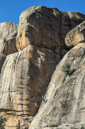 Rock climbers climbing El Indio, The Indian, in Manzanares El Real, on December 8, 2016. It is a granitic rock formation and a popular location for rock climbers. It is located in La Pedriza, Guadarrama Mountains National Park, province of Madrid, Spain
