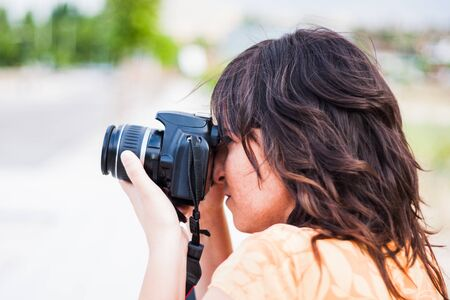 Photo for A young girl taking photograph with reflex camera - Royalty Free Image