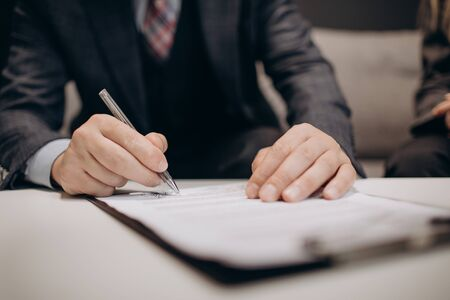 Photo pour Close up of mature businessman in stylish suit sitting on couch, holding pen and signing financial agreement. Concept of people, finance and cooperation. - image libre de droit