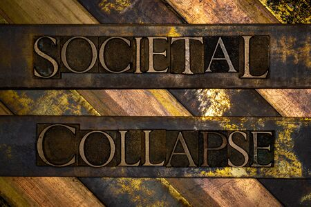 Photo of real authentic typeset letters Societal Collapse text on vintage textured grunge copper and gold background