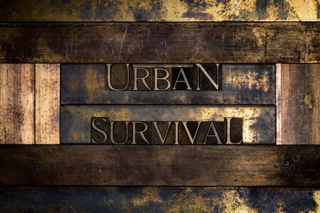 Photo of real authentic typeset letters Urban Survival text on vintage textured grunge copper and gold background